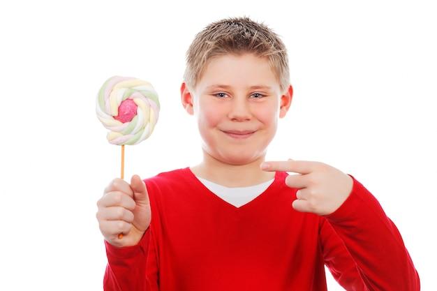 Портрет красивого радостного мальчика с леденцом на палочке