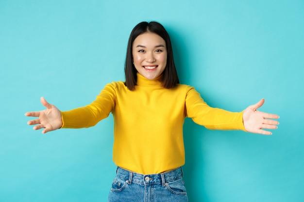 美しい韓国人女性の肖像画は、抱擁のために手を広げ、抱きしめるために手を伸ばし、カメラに微笑んで、あなたに挨拶し、青い背景の上に立っています。