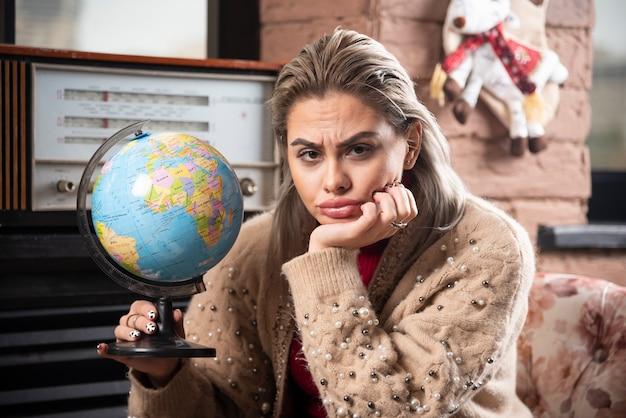 世界の地球を保持している美しい女性の肖像画