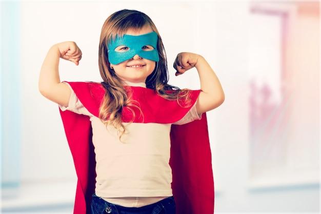 Портрет красивой маленькой девочки в костюме супергероя на светлом фоне