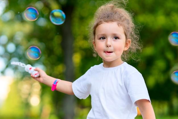 아름다운 어린 소녀의 초상화가 여름 햇살 가득한 공원에서 야외에서 즐거운 시간을 보내고 있고, 행복한 아이가 야외에서 비누방울을 불고 있습니다