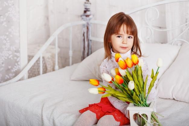 흰색과 노란색 튤립 꽃다발과 함께 침대에 앉아 아름다운 어린 소녀의 초상화