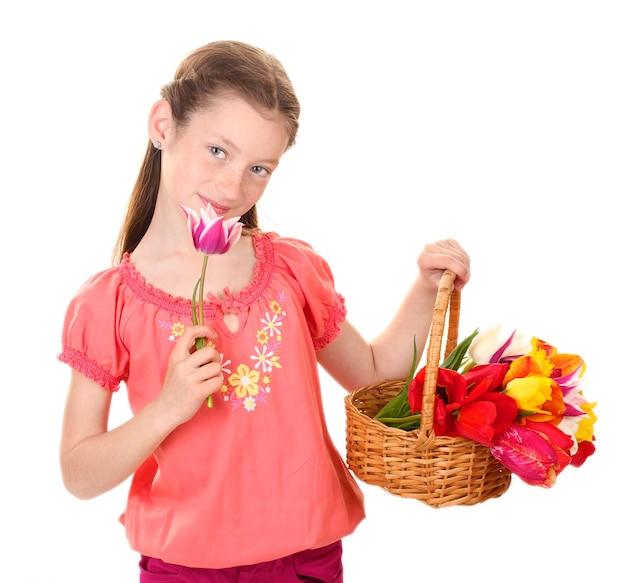Портрет красивой маленькой девочки с тюльпанами в корзине, изолированной на белом