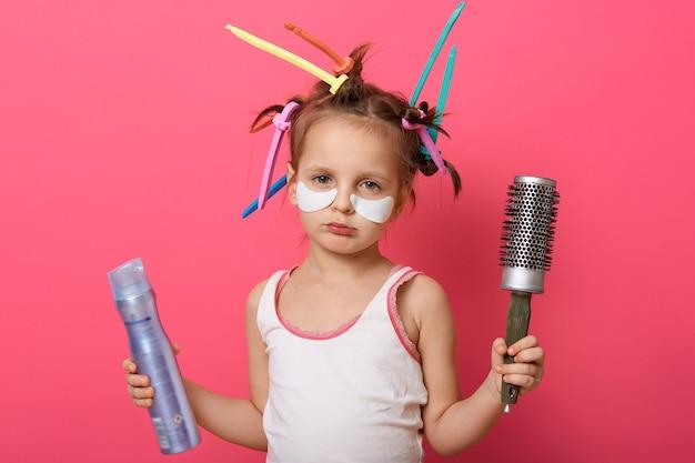 Портрет красивой маленькой улыбающейся девочки с лаком для волос в руках