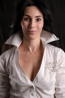 黒、コピースペースに分離された白いシャツを着た美しい成熟したブルネットの女性の肖像