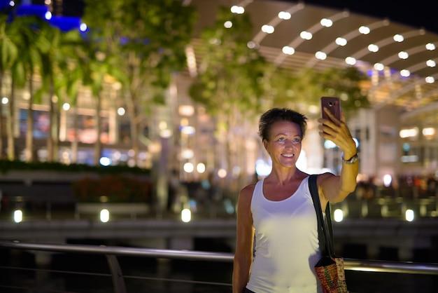 Портрет красивой зрелой туристической женщины, наслаждающейся жизнью во время путешествия по городу сингапур