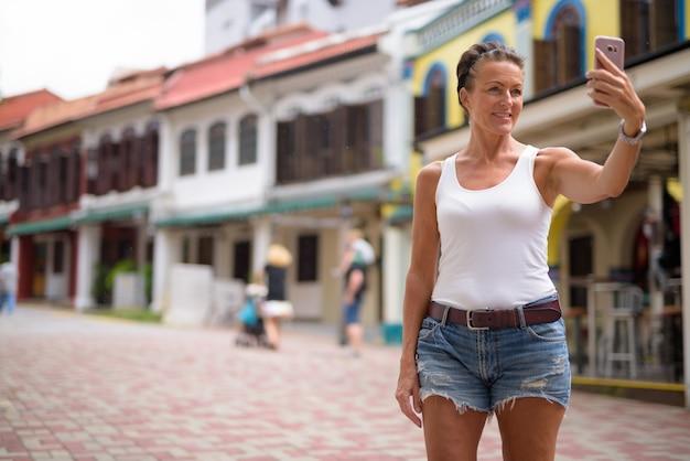 シンガポール市内旅行中に人生を楽しんでいる美しい成熟した観光客の女性の肖像