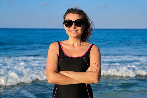 カメラを見て笑っているサングラス水着の美しい成熟した女性の肖像画。海の夕日の風景の背景。美容、健康、レジャー、ライフスタイルの人々の年齢の概念