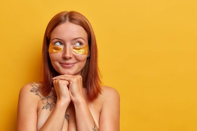 아름다운 중년 여성의 초상화는 턱 아래에 손을 유지하고, 신중하게 보이고, 부드럽고 매끄러운 피부를 즐기고, 빈 공간이있는 노란색 벽에 고립 된 미세한 선을 줄이기 위해 뷰티 패치를 착용합니다.