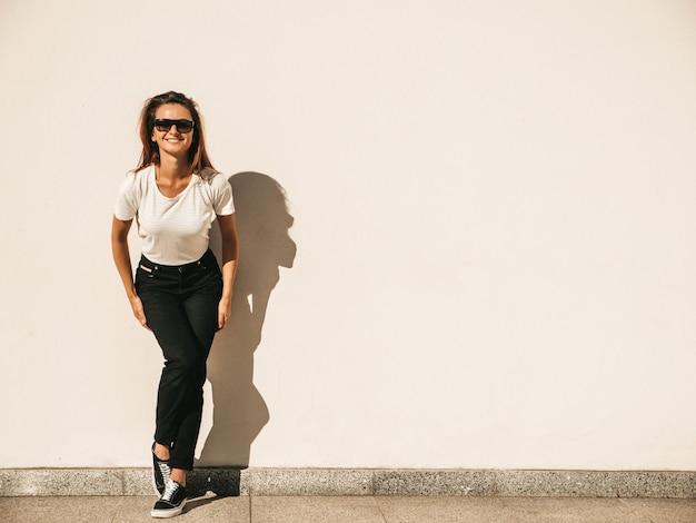 サングラスの美しいモデルの肖像画。夏の流行に敏感な白いtシャツとジーンズに身を包んだ女性。通りの壁の近くでポーズをとるトレンディな女性
