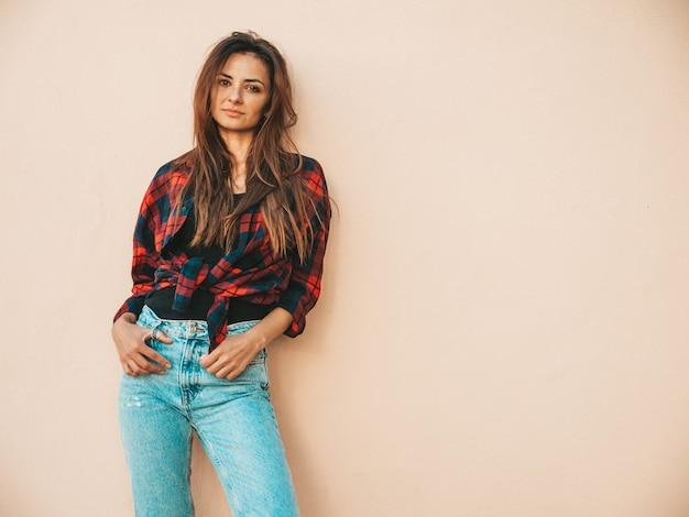 美しいモデルの肖像画。夏の流行に敏感な市松模様のシャツとジーンズに身を包んだセクシーな女性。通りの壁の近くでポーズをとるトレンディな女の子