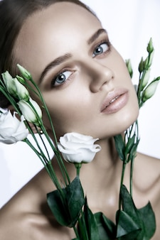 白いバラの花と白い背景に肌の良い美しいモデルの肖像画。