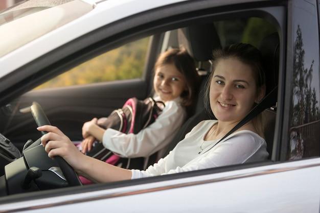 学校に娘と車を運転する美しい母親の肖像画