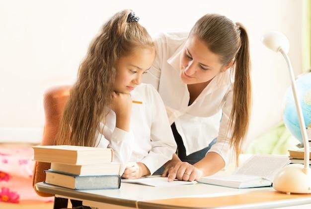 Портрет красивой матери, помогающей дочери делать домашнее задание