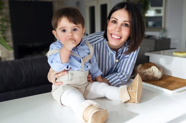 집에서 카메라를 보고 있는 아기와 함께 아름다운 어머니의 초상화.