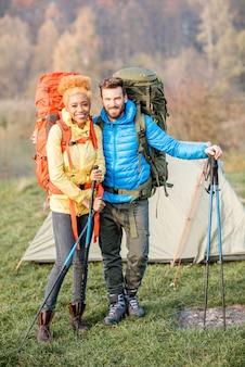 秋の緑の芝生のテントの近くのキャンプに立っているバックパックとスティックでハイキングする美しい多民族のカップルの肖像画