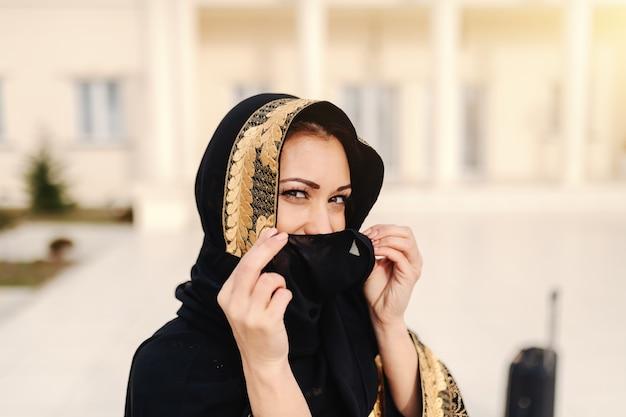 Портрет красивой мусульманской женщины покрывая ее сторону с шарфом пока стоящ outdoors.