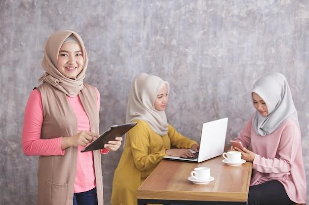 彼女の兄弟が自分のガジェットで忙しい間、笑顔でタブレットを持っている美しいイスラム教徒の女性の肖像画