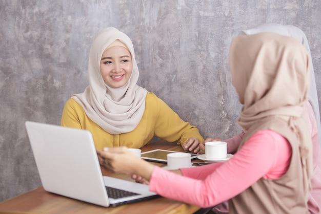 コーヒーショップで彼女のパートナーにラップトップでプロジェクトを説明する美しいイスラム教徒の女性の肖像画