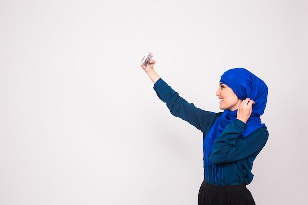 Hijab를 입고 아름 다운 이슬람 젊은 여자의 초상화는 그녀의 휴대 전화를 사용 하여 selfie를 가져가 라.