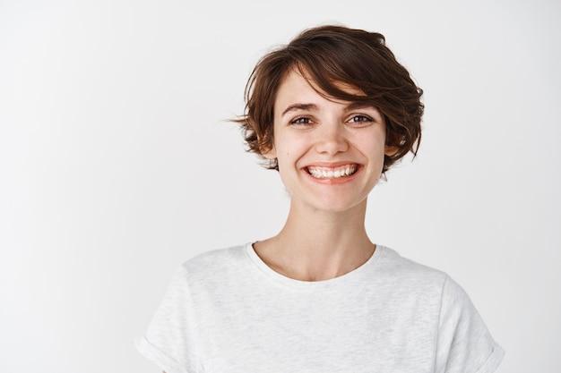 화장을 하지 않은 아름다운 자연 소녀의 초상화, 행복한 미소, 흰 벽에 티셔츠를 입고 서 있는