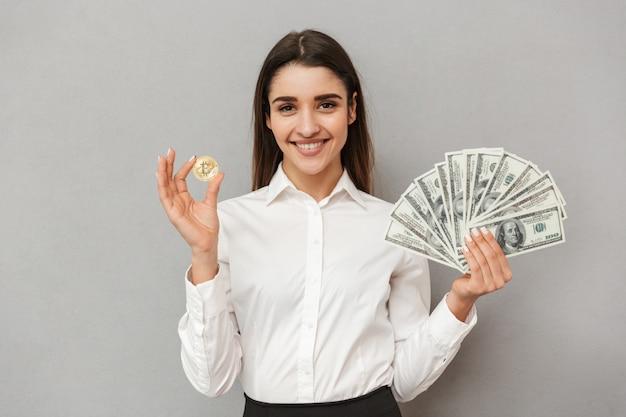 Портрет красивой офисной женщины с длинными каштановыми волосами в деловой одежде, показывающей биткойн и много долларовых купюр, изолированных на серой стене