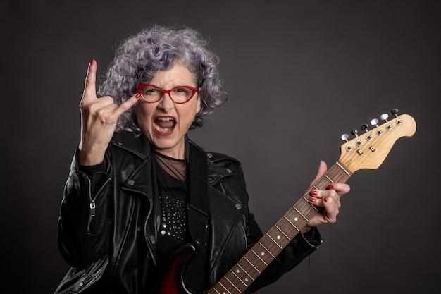 Портрет красивой пожилой женщины играет на электрогитаре