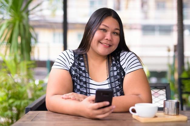 Портрет красивой полной азиатской женщины, расслабляющейся в кафе