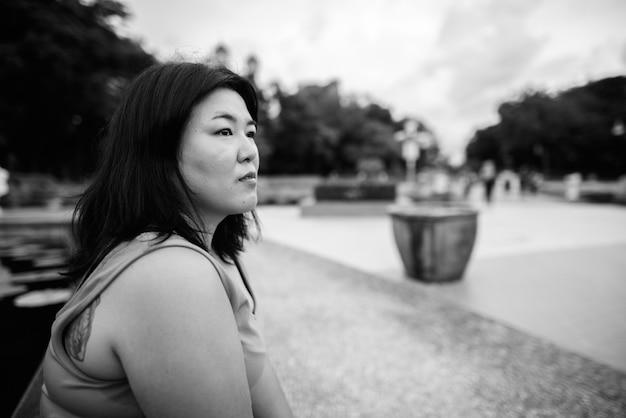 Портрет красивой полной азиатской женщины, расслабляющейся в парке в городе в черно-белом