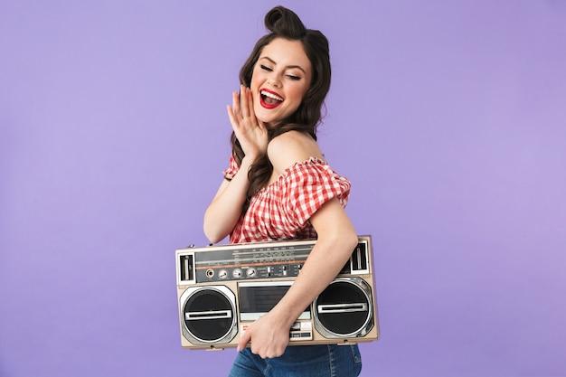 Портрет красивой женщины в стиле пин-ап в американском стиле радуется, держа в руках старый винтажный бумбокс, изолированный над фиолетовой стеной