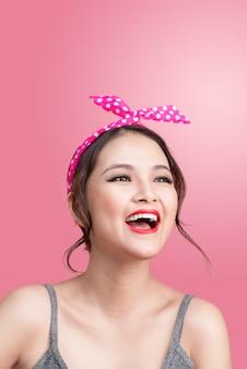 Портрет красивой женщины кинозвезды азиатской с винтажным составом и прической. изолированные на розовом фоне