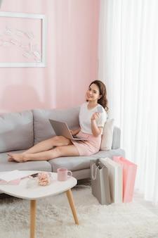 Портрет красивой позитивной дамы, смотрящей в сторону, поднимающей руку с кредитной картой, планирующей покупки в интернете, с ноутбуком на ногах, с приятным выражением лица.