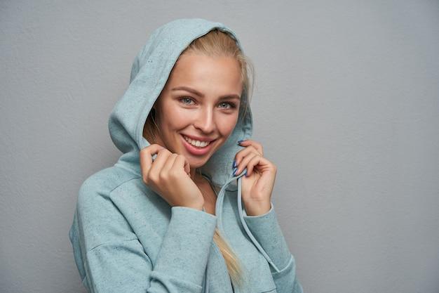 매력적인 미소와 후드와 함께 민트 스포티 한 코트에 밝은 회색 배경 위에 포즈 예쁜 파란 눈을 가진 아름 다운 긍정적 인 젊은 금발 아가씨의 초상화