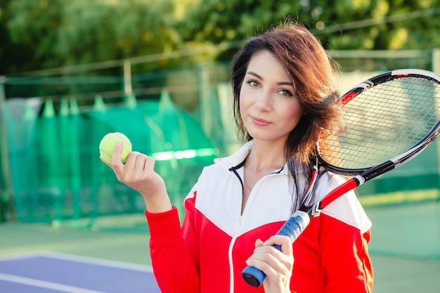 コートにラケットを持つ美しいかわいい女の子のテニスプレーヤーの肖像画。