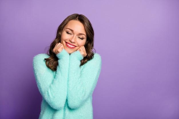 美しいきれいな女性の肖像画が頬骨に腕を組んで目を閉じて歯を見せる笑顔がふわふわのファジーミントパステルカラーのセーターの暖かさの柔らかさをお楽しみください。