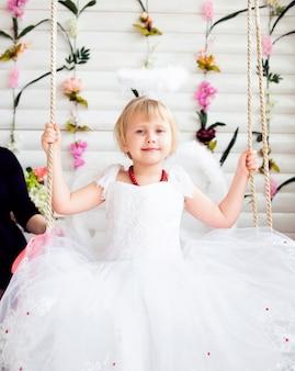 흰 후광과 날개를 가진 하얀 드레스를 입고 아름다운 공주 여자의 초상화 프리미엄 사진