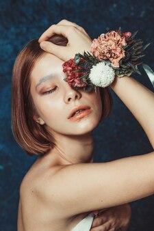 鈍いボブと花輪のブレスレットと美しい赤い髪の少女の肖像画