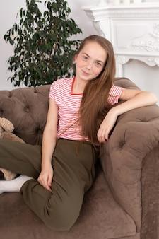 美しい赤毛の十代の少女の肖像画。笑顔のソファに座っているかわいい女の子