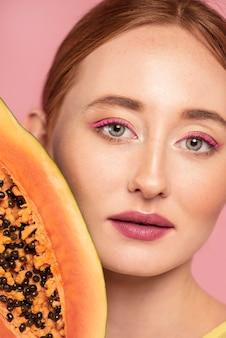 Портрет красивой рыжей женщины, держащей фрукт