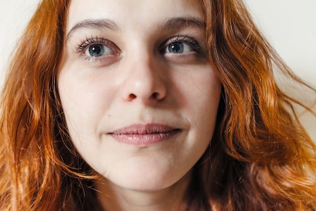 Портрет красивой рыжей женщины с вьющимися волосами крупным планом