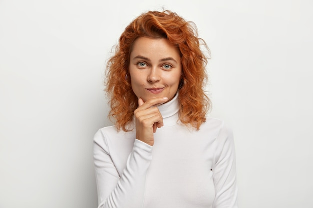 자연스러운 표정으로 아름다운 빨간 머리 여자의 초상화, 턱을 만지고 입술을 지갑