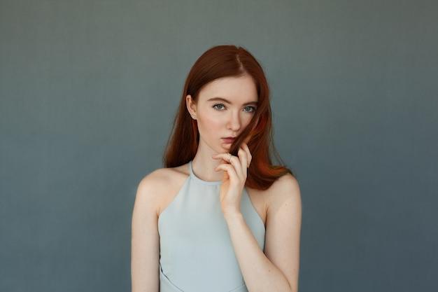 緑の目と自然メイクで美しい赤毛の若い女性モデルの肖像画、真剣な表情で見ている彼女の長い髪に触れます