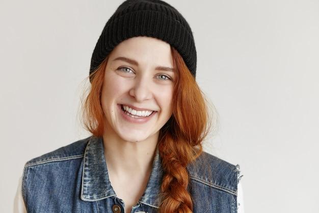 Портрет красивой рыжей молодой женщины в стильной черной шляпе и джинсовой куртке без рукавов