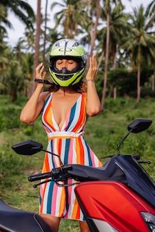 ヤシの木の下の熱帯のフィールドのジャングルで黄緑色のオートバイのヘルメットとカラフルな明るい夏のドレスの美しいライダーの女性の肖像画。