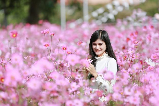 ピンクのコスモスの花が咲くコスモスの花畑、美しい鮮やかな自然の夏の庭の屋外公園で美しいロマンチックな女性の肖像画。