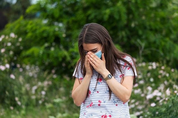 Портрет красивой грустной женщины в медицинской маске чихает среди белых цветов