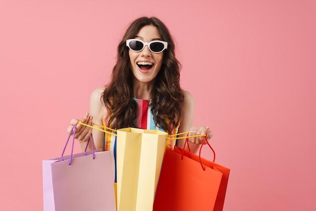 ピンクの壁に孤立してポーズをとって、買い物袋を持って、美しい悲鳴を上げる幸せな幸せな幸せな若いかわいい女性の肖像画