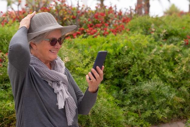 Портрет красивой старшей женщины в шляпе, стоящей в общественном парке, используя мобильный телефон в видеозвонке. улыбающаяся пожилая дама, одетая в серый цвет. кусты и цветы в фоновом режиме