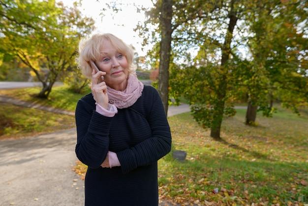 秋の屋外の公園でリラックスした短いブロンドの髪を持つ美しい年配の女性の肖像画