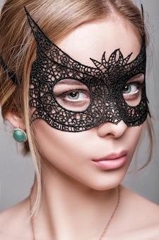 暗い背景に黒いレースマスクで緑の目を持つ美しい官能的な金髪の女性の肖像画。ベネチアンマスク